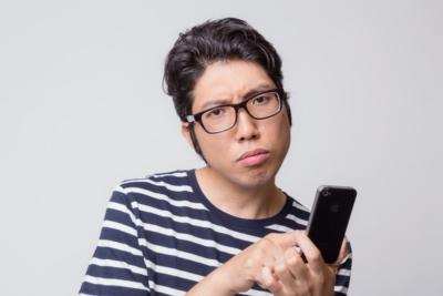 アプリの使い方がわからなくて困惑する男性 [モデル:紳さん]